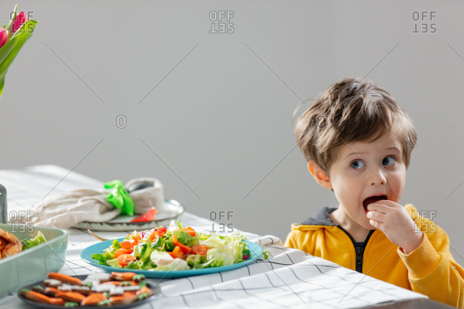 Little boy sitting at easter dinner table and eating a salad