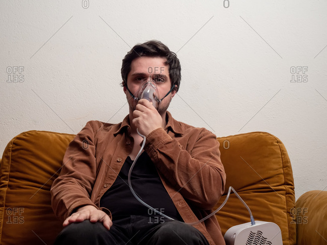 Guy sitting on couch at home and breathe with a respirator mask