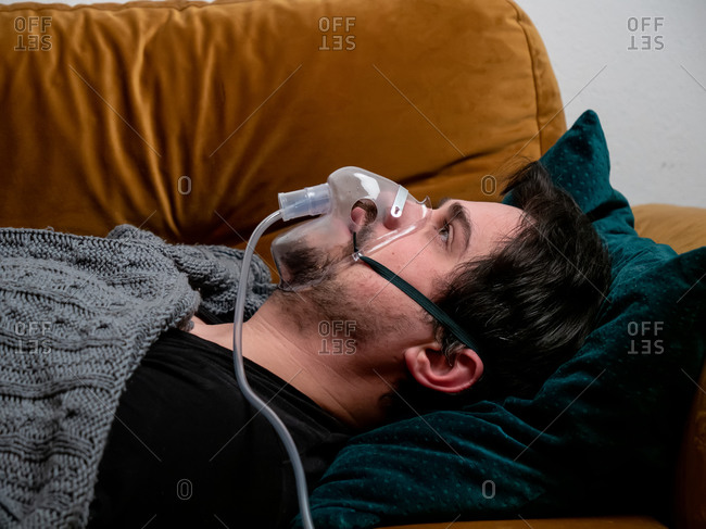 Guy lying on couch at home and breathe with a respirator mask