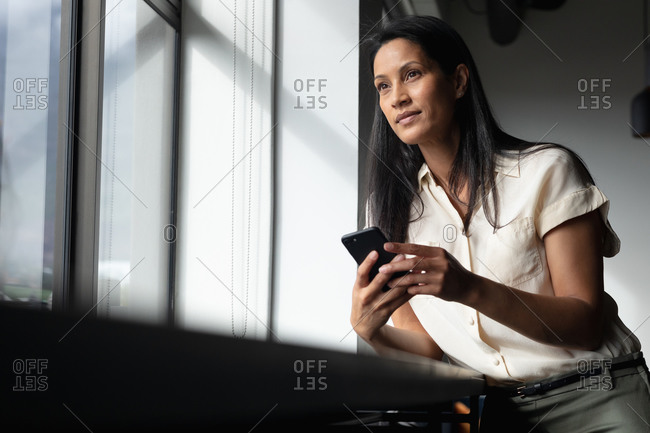 Mixed race businesswoman standing by window using smartphone in modern office. business modern office workplace technology.