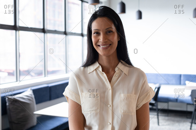 Portrait of mixed race businesswoman standing looking at camera and smiling in modern office. business modern office workplace technology.