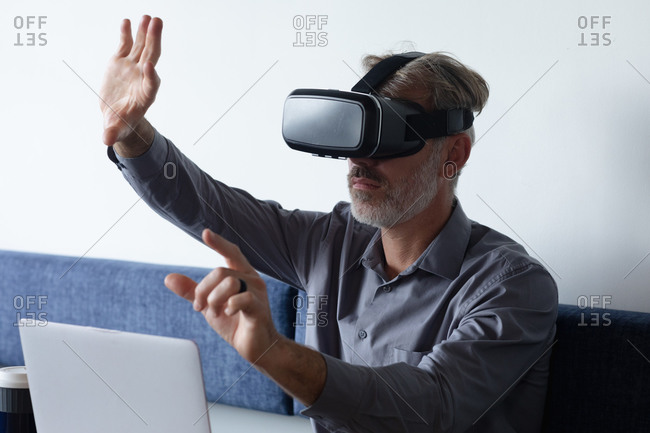Caucasian businessman sitting using vr googles and laptop in modern office. business modern office workplace technology.