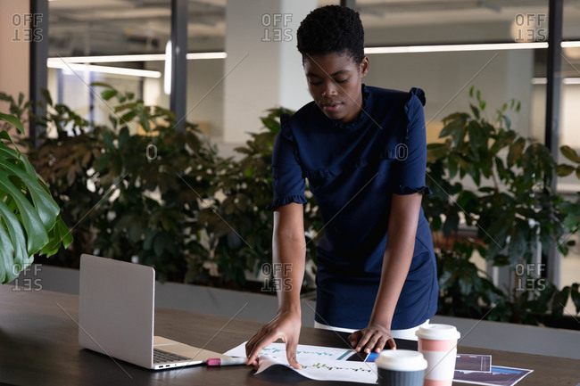 Mixed race businesswoman standing using laptop going through paperwork in modern office. business modern office workplace technology.