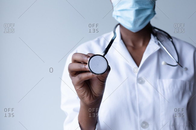 Mixed race female doctor wearing face mask standing and using a stethoscope. medical professional healthcare worker hygiene during coronavirus covid 19 pandemic.