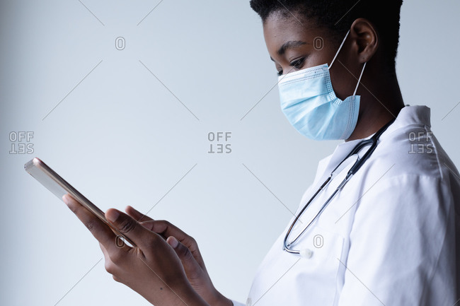 Mixed race female doctor wearing face mask standing and using digital tablet. medical professional healthcare worker hygiene during coronavirus covid 19 pandemic.