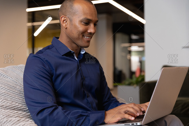 Mixed race businessman sitting using laptop in a modern office. business modern office workplace technology.