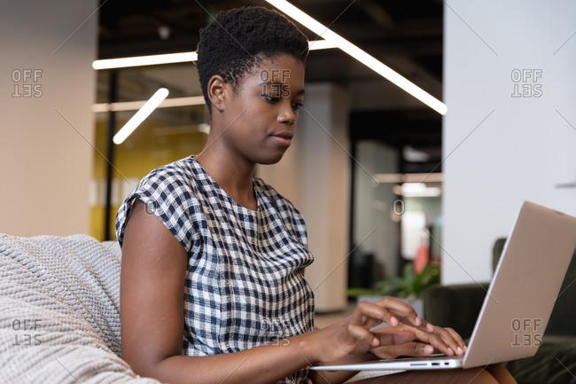 Mixed race businesswoman sitting using laptop in a modern office. business modern office workplace technology.