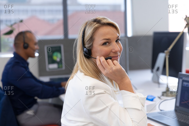 Caucasian businesswoman sitting wearing headphones looking at camera and smiling in modern office. business modern office workplace technology.