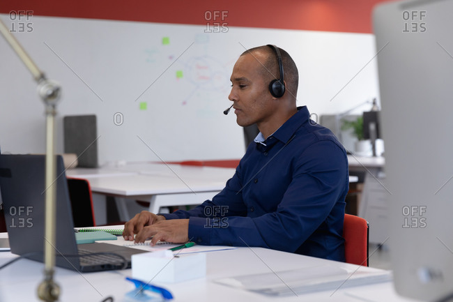 Mixed race businessman sitting wearing headphones using laptop in modern office. business modern office workplace technology.
