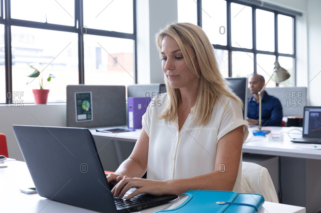 Caucasian businesswoman sitting using a laptop in a modern office. business modern office workplace technology.