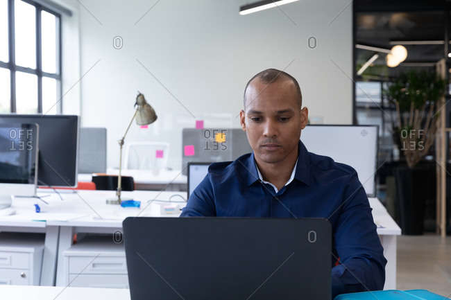 Mixed race businessman sitting using a laptop in a modern office. business modern office workplace technology.