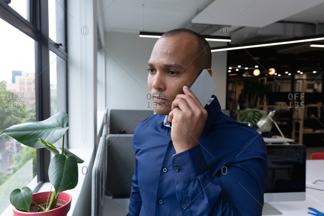 Mixed race businessman standing by window using smartphone in a modern office. business modern office workplace technology.