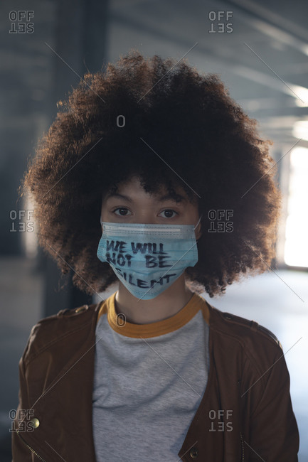 Mixed race woman wearing face mask with slogan looking at the camera. gender fluid lgbt identity racial equality concept.