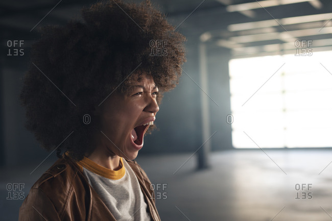 Mixed race woman standing in empty building and shouting. gender fluid lgbt identity racial equality concept.