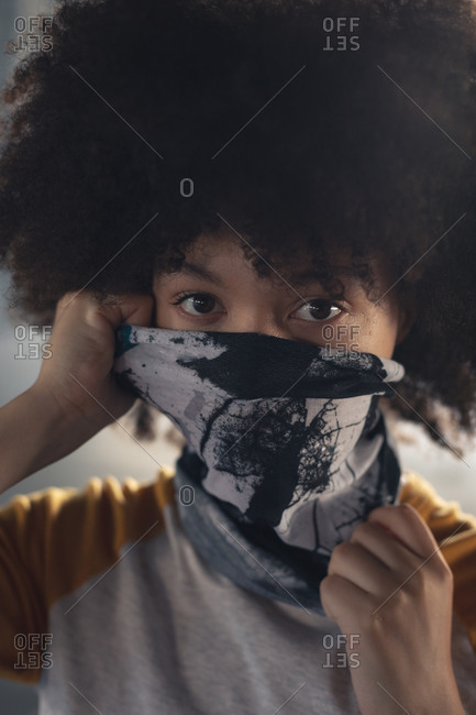 Mixed race woman putting a face mask on looking at the camera. gender fluid lgbt identity racial equality concept.