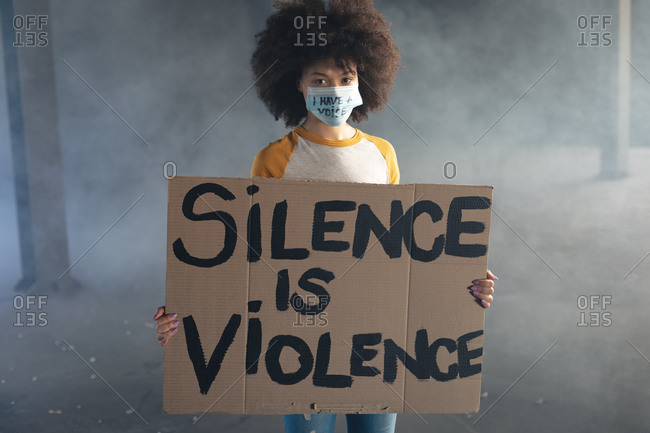 Mixed race woman wearing face mask with slogan holding protest sign. gender fluid lgbt identity racial equality concept.