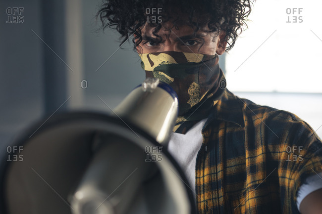 Mixed race man wearing face mask shouting in megaphone. gender fluid lgbt identity racial equality concept.