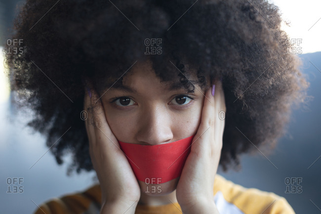 Mixed race woman with tape on mouth looking at camera. gender fluid lgbt identity racial equality concept.