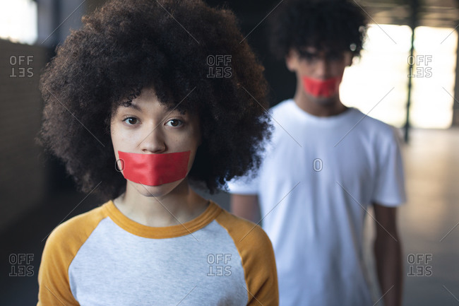 Mixed race man and woman with tape on mouth looking at camera. gender fluid lgbt identity racial equality concept.