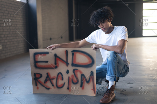 Mixed race man holding protest sign looking at camera. gender fluid lgbt identity racial equality concept.