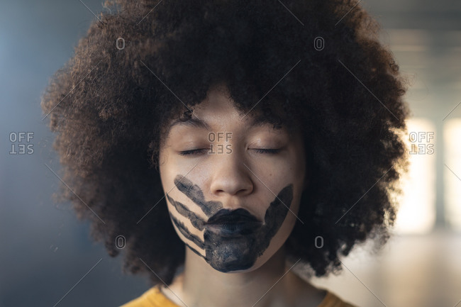 Mixed race woman having a black hand print painted on face. gender fluid lgbt identity racial equality concept.