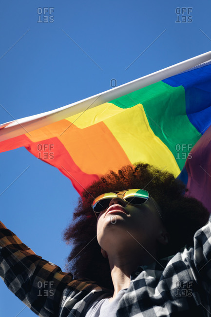 Mixed race woman standing on rooftop holding rainbow flag. gender fluid lgbt identity racial equality concept.
