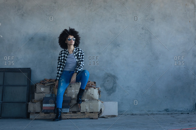 Mixed race woman in an empty building wearing sunglasses. gender fluid lgbt identity racial equality concept.