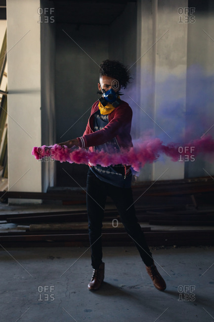 Mixed race man wearing face mask holding a purple flare. gender fluid lgbt identity racial equality concept.