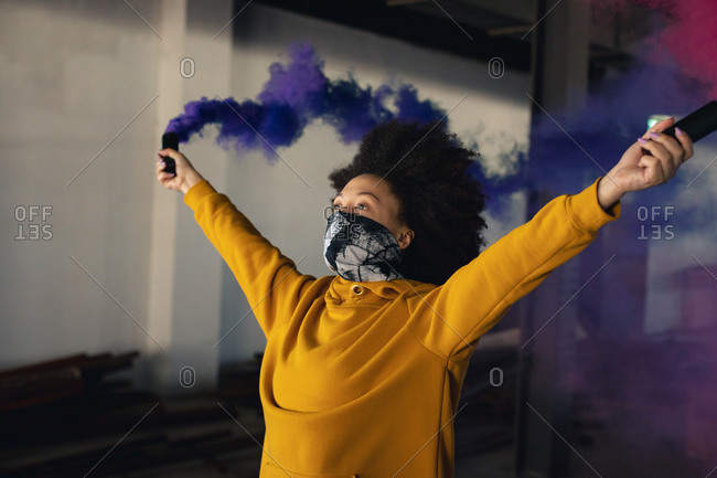 Mixed race woman wearing face mask holding a blue flare. gender fluid lgbt identity racial equality concept.
