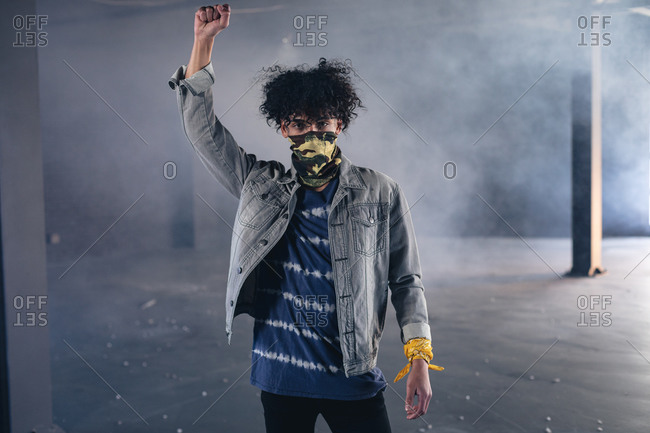 Mixed race man in an empty building wearing face mask raising fist. gender fluid lgbt identity racial equality concept.