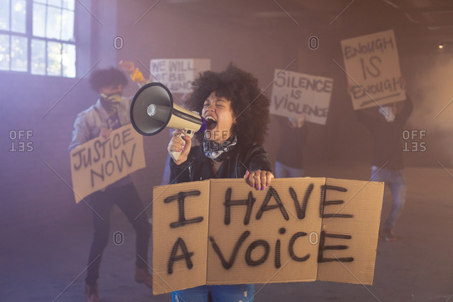 Mixed race woman shouting in megaphone holding protest sign. with protesters in the background. gender fluid lgbt identity racial equality concept.
