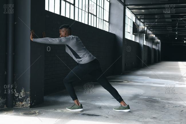 African American man leaning on a wall in an empty urban building and stretching. urban fitness healthy lifestyle.