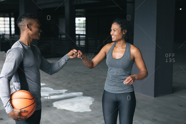 African American man and woman standing in an empty urban building and fist bumping. urban fitness healthy lifestyle.