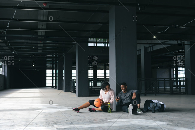 African American man and woman sitting in empty urban building and resting after playing basketball. using smartphone and laughing. urban fitness healthy lifestyle.