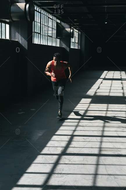 African American man wearing sports clothes jogging in empty urban building. urban fitness healthy lifestyle.