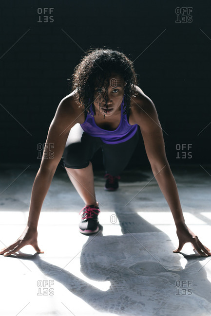 African American woman wearing sports clothes kneeling starting to run in empty urban building. urban fitness healthy lifestyle.