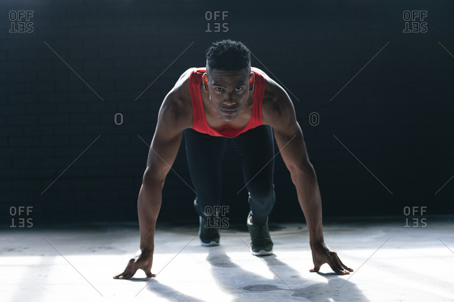 African American man wearing sports clothes kneeling starting to run in empty urban building. urban fitness healthy lifestyle.