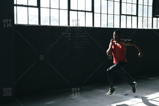African American man wearing sports clothes sprinting in empty urban building. urban fitness healthy lifestyle.