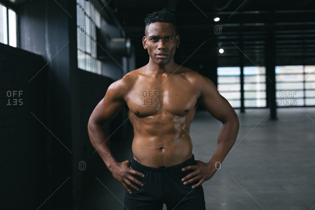 African American man standing and flexing his muscles in empty urban building. urban fitness healthy lifestyle.