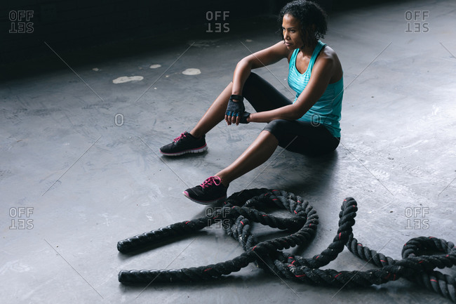 African American woman wearing sports clothes sitting resting after battling ropes in empty urban building. urban fitness healthy lifestyle.