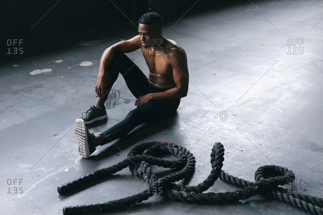 African American man wearing sports clothes sitting resting after battling ropes in empty urban building. urban fitness healthy lifestyle.