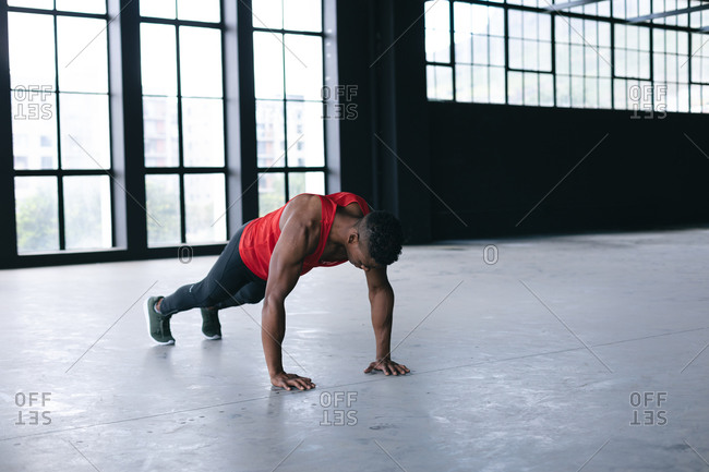 African American man wearing sports clothes doing push ups in empty urban building. urban fitness healthy lifestyle.