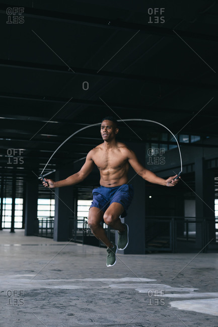Portrait of African American man skipping the rope in empty urban building. urban fitness healthy lifestyle.