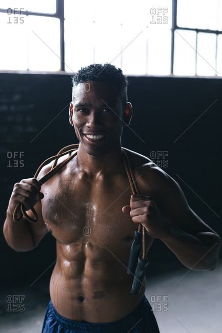 Portrait of African American man having skipping rope over his shoulders in empty urban building. looking at the camera and smiling. urban fitness healthy lifestyle.