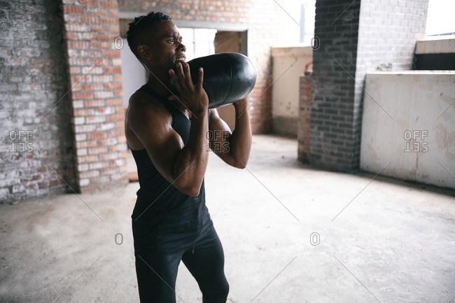 African American man exercising with a medicine ball in empty urban building. urban fitness healthy lifestyle.