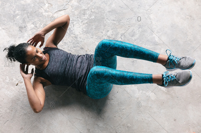 African American woman wearing sports clothes exercising doing crunches in empty urban building. urban fitness healthy lifestyle.