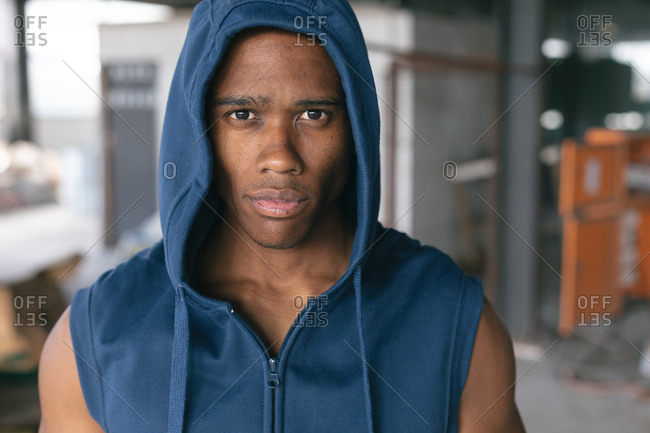 Portrait of African American man wearing hoodie looking at camera in empty urban building. urban fitness healthy lifestyle.