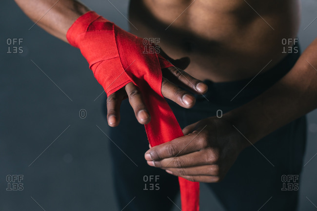 African American man tightening the tourniquet in an empty urban building. urban fitness healthy lifestyle.
