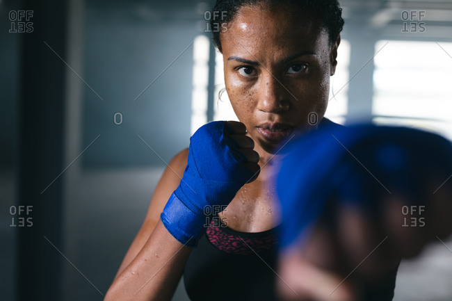 African American woman throwing punches in the ar in an empty urban building. urban fitness healthy lifestyle.