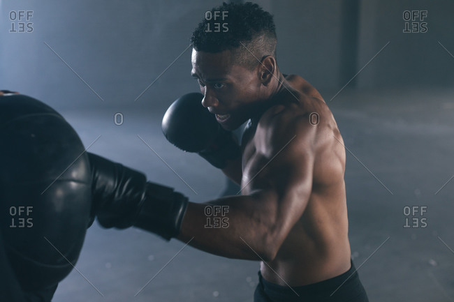 African American man wearing boxing gloves punching boxing bag in an empty urban building. urban fitness healthy lifestyle.